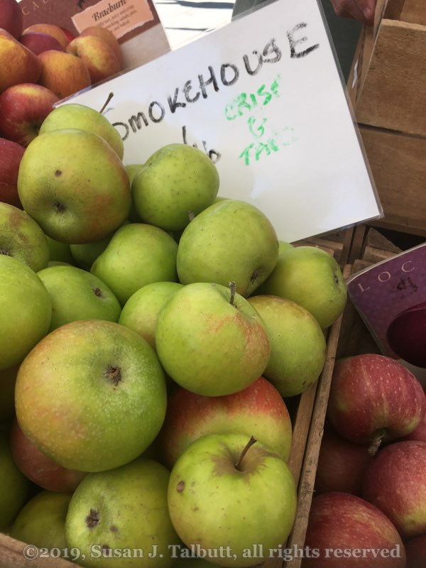 Green-skinned apples in a crate, with a hand-written sign behind.