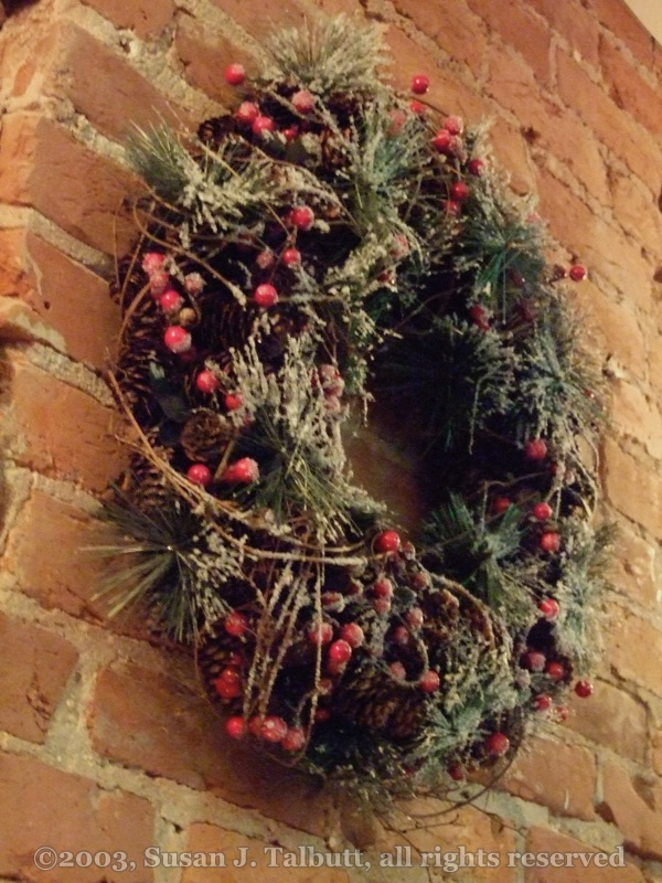 [Large wreath of evergreens and red berries hanging on a brick wall, Copyright 2009]