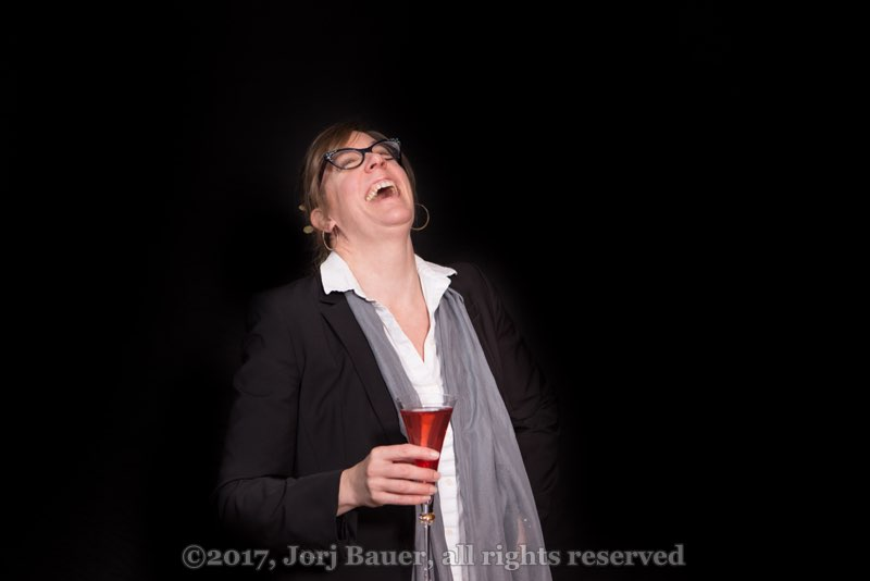 Middle-aged woman holding a red-orange cocktail in a champagne flute, throwing her head back and laughing