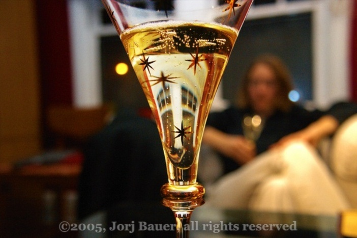 [Glass of champagne in the foreground, out-of-focus woman in the background; copyright 2005, Jorj Bauer, all rights reserved]