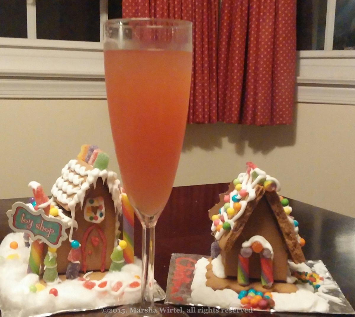[Red lion cocktail in a champagn flute next to two of the cutest gingerbread houses; copyright 2015, Marsha Wirtel, all rights reserved]